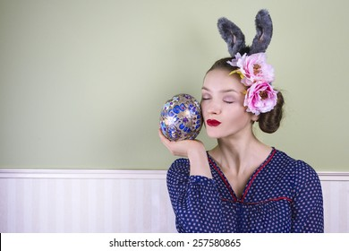 Young lady with bunny ears holding a large easter egg