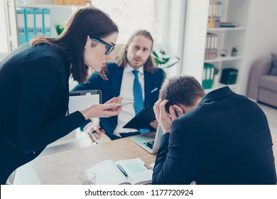 Young lady chief boss in glasses wearing jacket having quarrel with employees about overdue financial report at work place, work station, businesspeople. Bullying concept