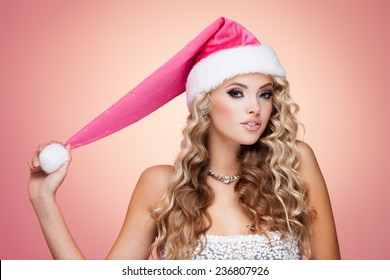 Young lady in Christmas hat on pink background