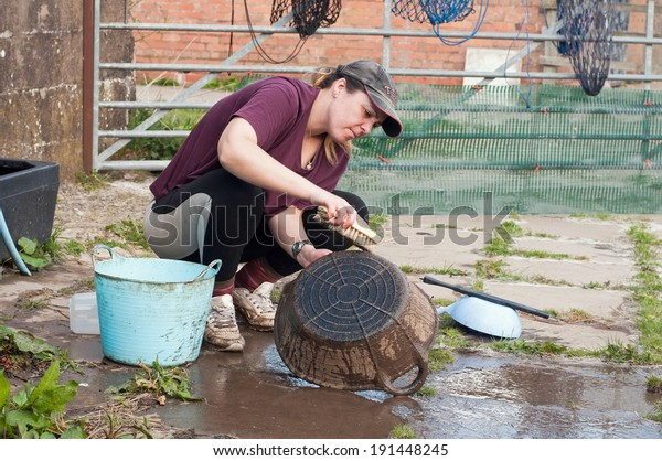 Young lady cleaning her muddy buckets.