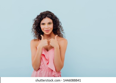 "young lady with curly hair without the ""ok"" sign, pick up big fingers up, dressed in pink, isolated blue background, positive facial emotions, copy space"