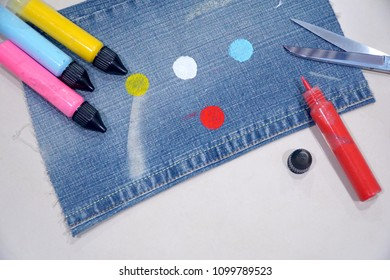 Young lady cut jean from her old pant and paint 3 circle colors. Prepare to make a  bag. Idea, DIY, Reuse, Handmade concept. Beauty / fashion.