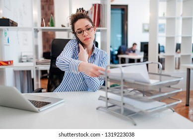 Young lady at desk doing paperwork and talking on smartphone.