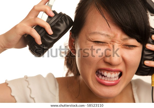 young lady disturbed by loud music on white background