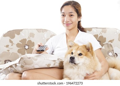 Young lady and a dog watching and enjoying a television program.