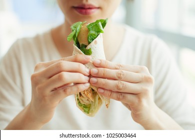 Young lady eating healthy chicken salad wrap