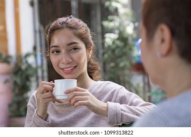 Young lady enjoying a cup of coffee with a friend. Oudoor shot
