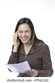 Young lady of filipino ethnicity,is sitting on stool with a white background.She is read a document.Also listening on the telephone and smiling with some good news.