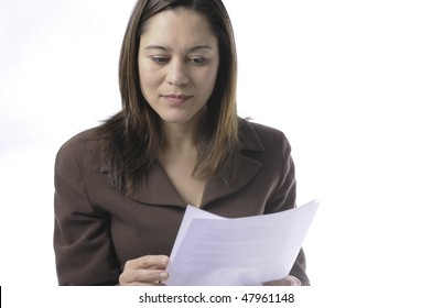 Young lady of filipino ethnicity,is sitting on stool with a white background.She is read a document.It has two pages.Photo is just above the waist.