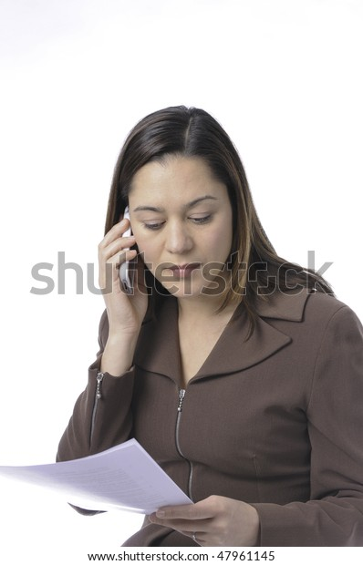 Young lady of filipino ethnicity,is sitting on stool with a white background.She is read a document.Also listening on the telephone.