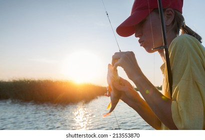 Young lady fishing perch on the river at sunset