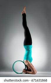 young lady fitness student handstand on floor stretching legs with body and using hands pulling pilate ring in grey background.