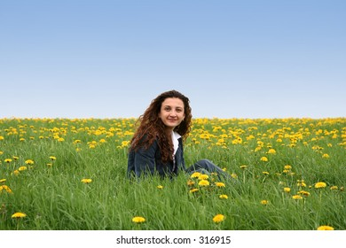 A young lady in a flowering spring field