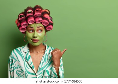 Young lady gives tipes how to look young and beautiful, points thumb away on blank space, grooming with hair rollers, applies green beauty mask for reducing fine lines. Hair care and wellness concept