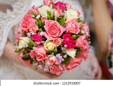 Young lady in gorgeous wedding dress holding a bouquet of pink and white roses in her hands. Wedding or engagement concept