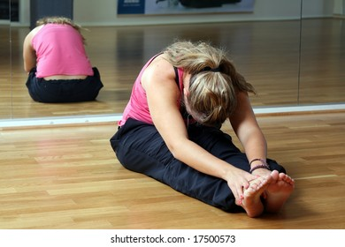 Young lady at the gym in sports position stretching