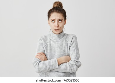Young lady with hair in topknot standing with arms folded looking up. Capricious female model in grey dress biting lips thinking about her desire.  Daydream concept
