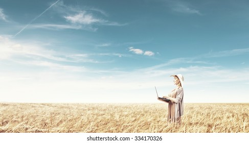 Young lady in hat and long dress using laptop