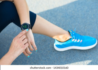 Young lady with healthy lifestyle, verifying heart rate on smart watch after training or exercise on race track