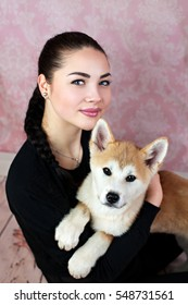 Young Lady With Her Cute Akita Puppy
