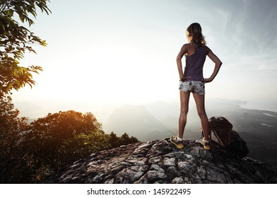 Young lady hiker with backpack enjoying sunrise from top of a mountain