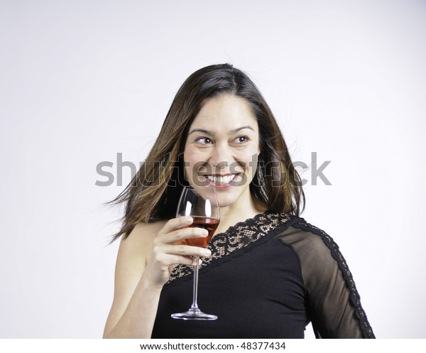 Young lady holding a glass of wine and a big smile. She is of mixed ethnicity.