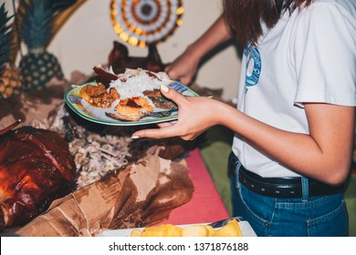Young lady holding a plate of Filipino food while slicing a piece of meat of the pork roast or also known as Lechon  de leche.
