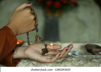 Young lady holding rosary in hand. Female hands praying holding a rosary with Jesus Christ Cross or Crucifix. Junior woman with Christian Catholic religious symbol of faith.