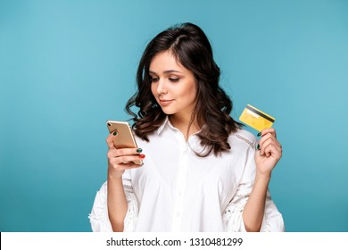 young lady isolated over blue background using mobile phone holding credit card.