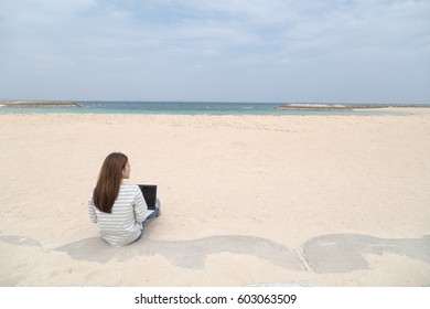 Young lady and laptop on the beach