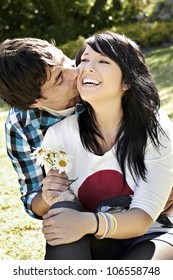 Young lady laughing while young man kisses and gives her flowers