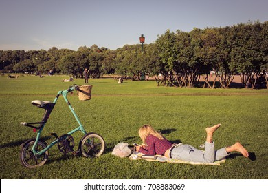 Young lady lays in the park and sky blue bicycle standing on gra