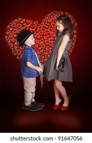Young lady and little gentleman confession in love at the burgundy background with shining  heart