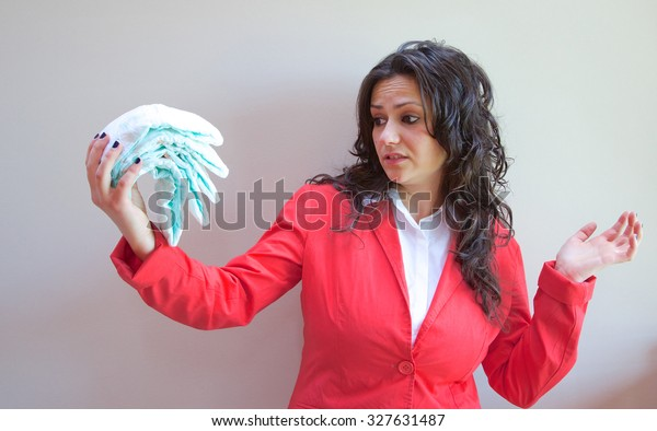 A young lady looks with disgust at a pile of diapers