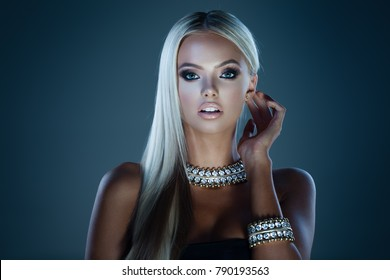 Young lady with luxury accessories on dark blue background