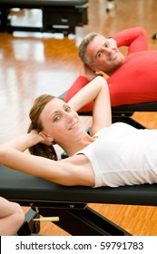 Young lady making sit-ups on bench at gym