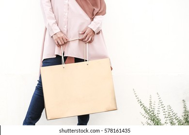 Young lady in modern muslim attire holding a golden paper bag isolated with white background.