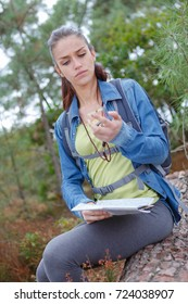 young lady orienteering holding map and compass