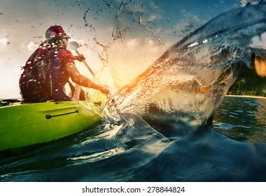 Photo of Young lady paddling hard the kayak with lots of splashes