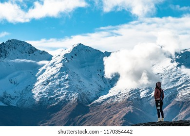 A young lady photographer with a stunning  scenery of rocky mountain covered with snow after the raining day. Cloudy and foggy. Diamond lake track, Wanaka, New Zealand.