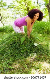 Young lady piling up fresh mowed grass as food for animals