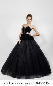 young lady posing in fashion long black dress