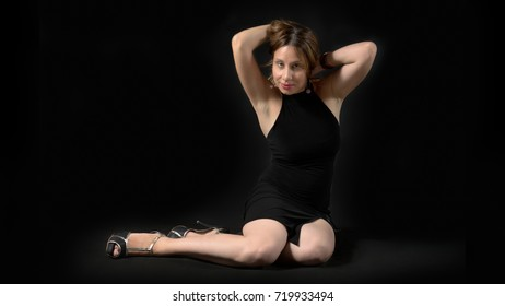 young lady posing on the floor, wearing a black tight mini dress and high heels, having both hands in her hair