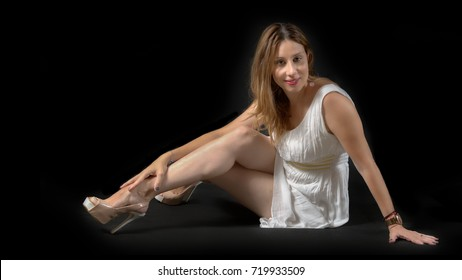 young lady posing on the floor, wearing a white mini dress and high heels