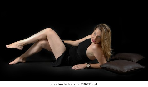 young lady posing on the floor, wearing a black tight mini dress and barefoot, with her high heels in view