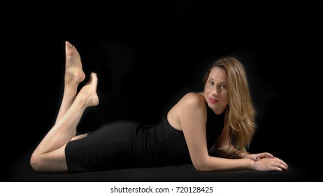young lady posing on the floor, wearing a black tight mini dress and barefoot