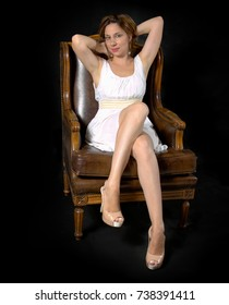 young lady posing sexy in armchair
