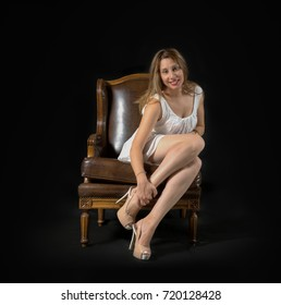 young lady posing sitting in an armchair, wearing a white mini dress and high heels