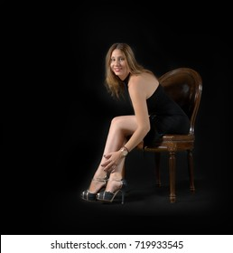 young lady posing sitting on a wooden chair, wearing a black tight mini dress and high heels