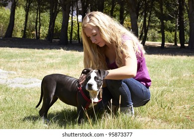 Young lady putting leash on Pit Bull dog breed